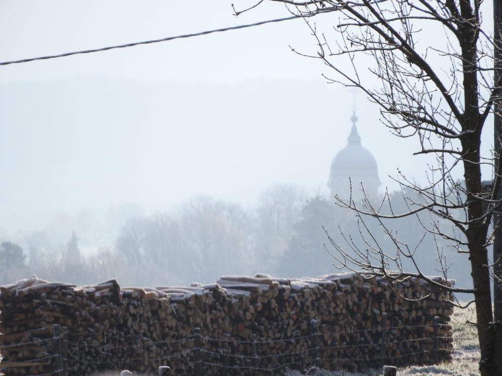 La silhouette du clocher de Bucey dans la brume matinale
